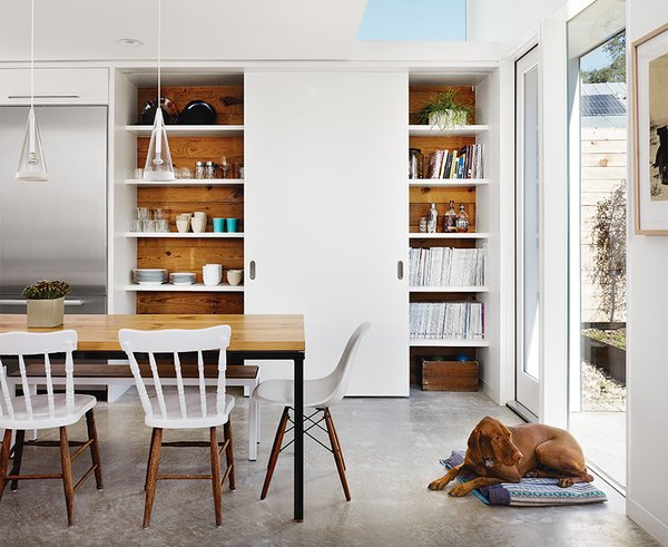 Featuring reclaimed wood from the original house, a single sliding door covers only half of the kitchen pantry. As the door slides, china and glassware are revealed on one side; the other side holds Anne's design library and favored heirlooms. The sliding door follows a track installed in the concrete underfloor; the shelves are supported by recessed steel brackets, strong enough to hold the weight of a man—or a baby. An additional full-size pantry is located inside the laundry room, toward the original bungalow.