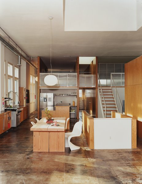 The kitchen and dining area is furnished with a salvaged timber table designed by Matt Eastvold, white Panton chairs, and a Glo Ball pendant lamp.