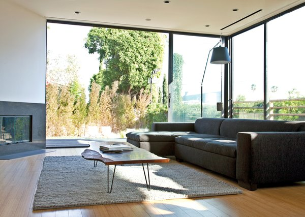 The sofa is from Cantoni, the rug is from Restoration Hardware, and the Tolomeo floor lamp is by Michele   De Lucchi for Artemide. The large windows in the background and throughout the house are from Western Window Systems.