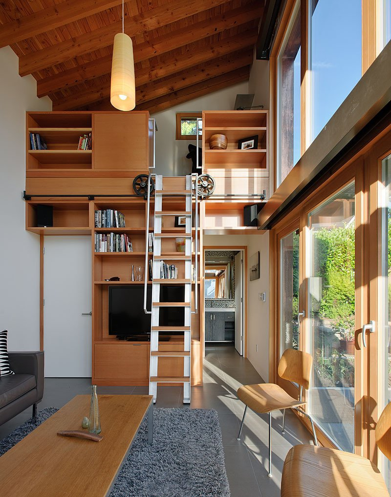 A rolling ladder made from salvaged wood and components leads to a small, yet well equipped, office.  shelves from Garden Pavilion, Seattle