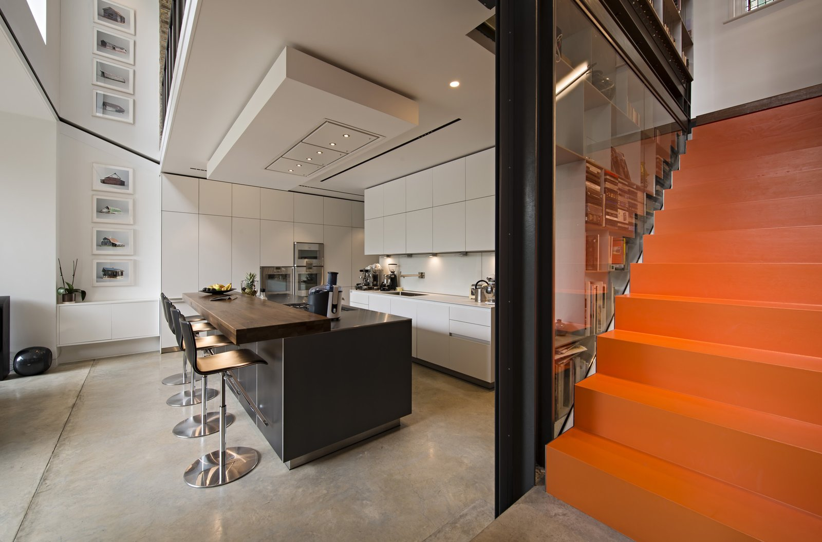 The stairs roll out into the kitchen and dining areas. The individual steps are steel trays dipped in orange liquid rubber, to squeaky effect.  190+ Best Modern Staircase Ideas from This Dramatic London Renovation Boasts a Five-Story Bookcase