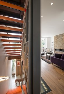This cross-section of stairwell and library structure creates a shard of light for rooms on every level. At nighttime, LED bulbs under the handrails emit a glow.