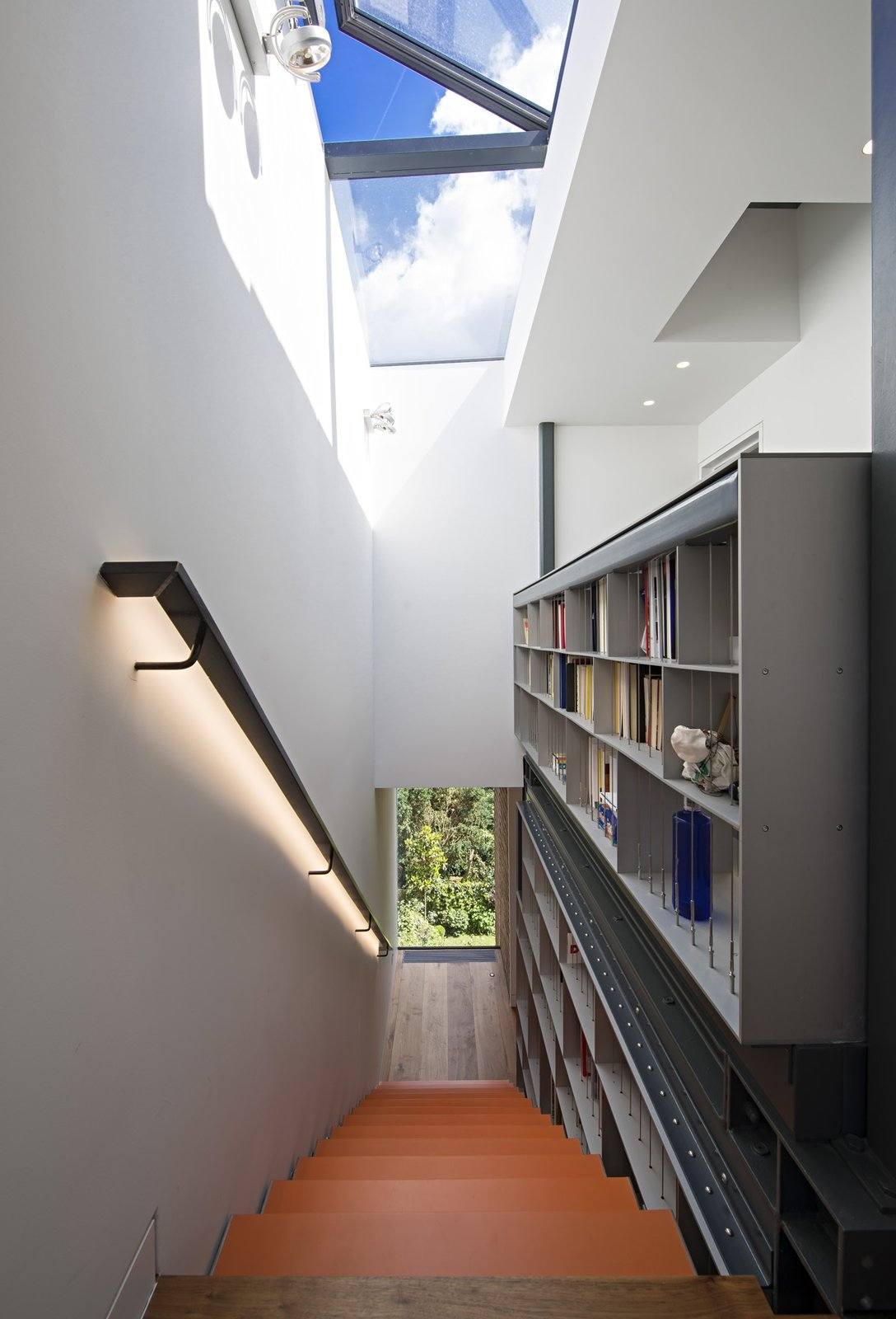 Reaching for the skylight, the five-story staircase is met at the top by the custom bookcase. The skylight opens and closes automatically in response to temperature and weather. This integrated structure is the spine of the house, off of which all other spaces are arranged.  190+ Best Modern Staircase Ideas from This Dramatic London Renovation Boasts a Five-Story Bookcase