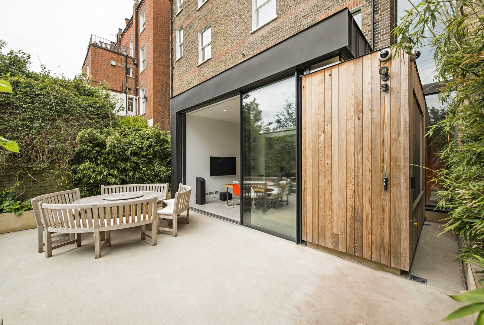 """Doors, Metal, Exterior, and Sliding Door Type Looking back on the home from the concrete patio, its verticality becomes apparent. The zinc, cedar, and glass extension erupts from the base of the old brick envelope—diminutive but disruptive.  Search """"concrete"""" from This Dramatic London Renovation Boasts a Five-Story Bookcase"""