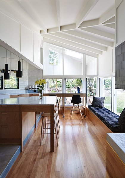 The architects used blackbutt wood for the flooring and Whisper White paint by Dulux throughout the interior. An A110 Hand Grenade Pendant Lamp, by Alvar Aalto for Artek, hangs above the white Carrara marble-topped island.