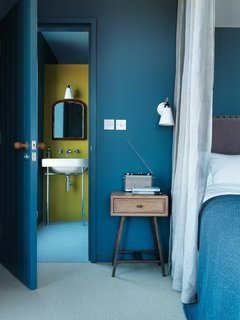 """The bed and side table in the master bedroom are from Loaf. In the adjacent bathroom, an antique mirror hangs above a Duravit sink. """"There's a slight Arts and Crafts feel to it,"""" says Marston of the house."""