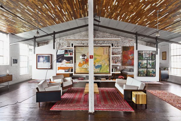 Beneath a recycled-wood ceiling and centered by a Bokhara rug, the living area contains furniture of their own design.
