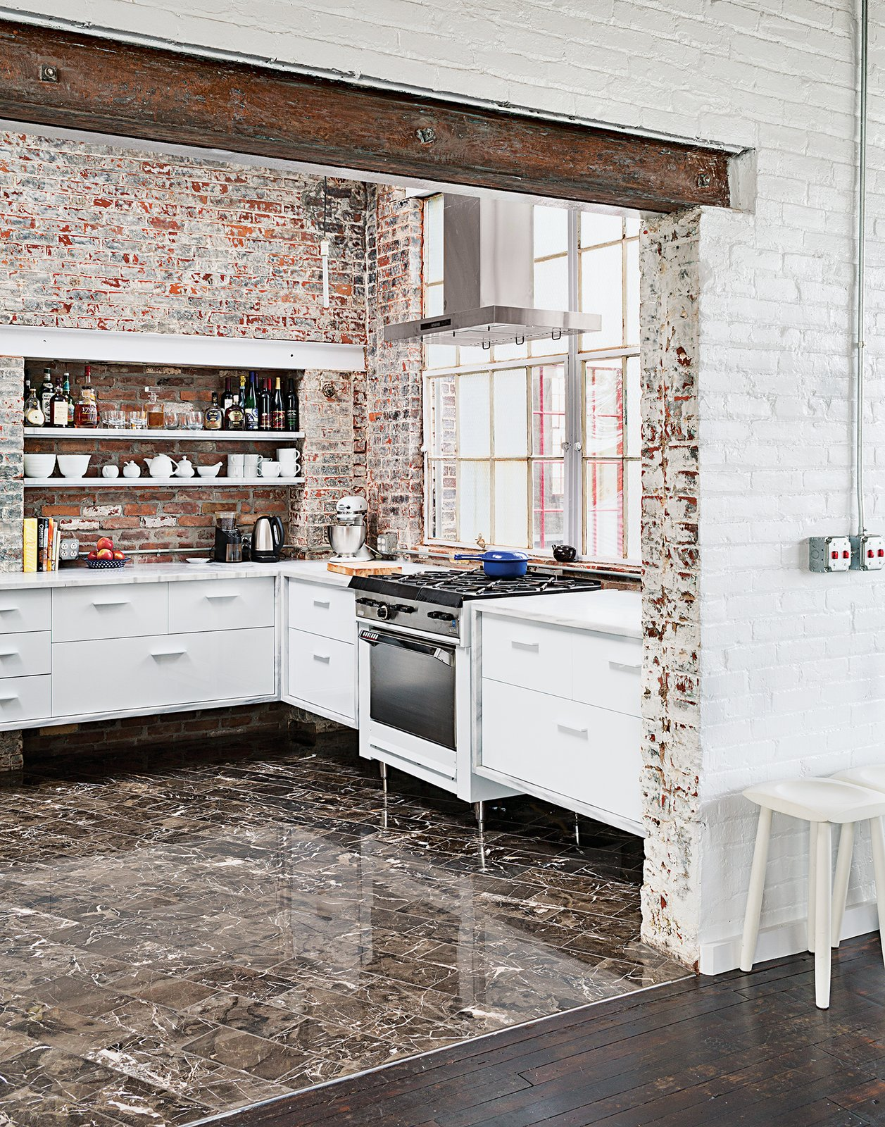 Kitchen, Brick Backsplashe, and White Cabinet Among the couple's cost-saving measures was outfitting the kitchen with their own custom cabinetry. The brick and windows are original, the Garland stove was a Craigslist find, and the floor tile was found on closeout at a cost of about $1 per square foot.  Modern Ways to Use Brick by Allie Weiss