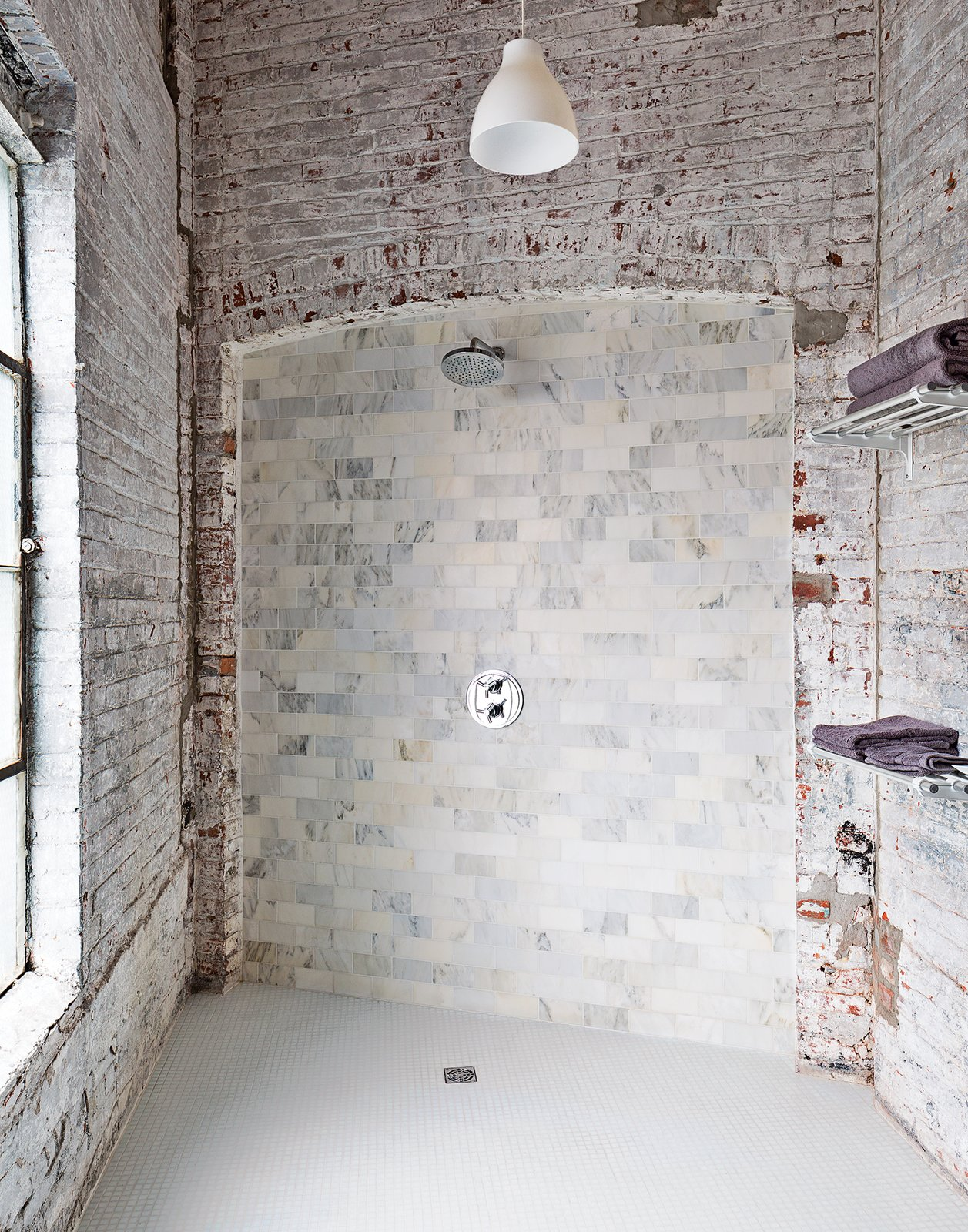 """Bath Room and Open Shower The bathroom evokes the building's industrial bones. The pendant light is from Ikea, and the towel racks are repurposed train car luggage racks. The Carrara tiles are mismatched seconds. """"It works if you let yourself not try to fix it,"""" says Brandon.  Best Photos from A Design Duo Takes Over A Whole Factory"""