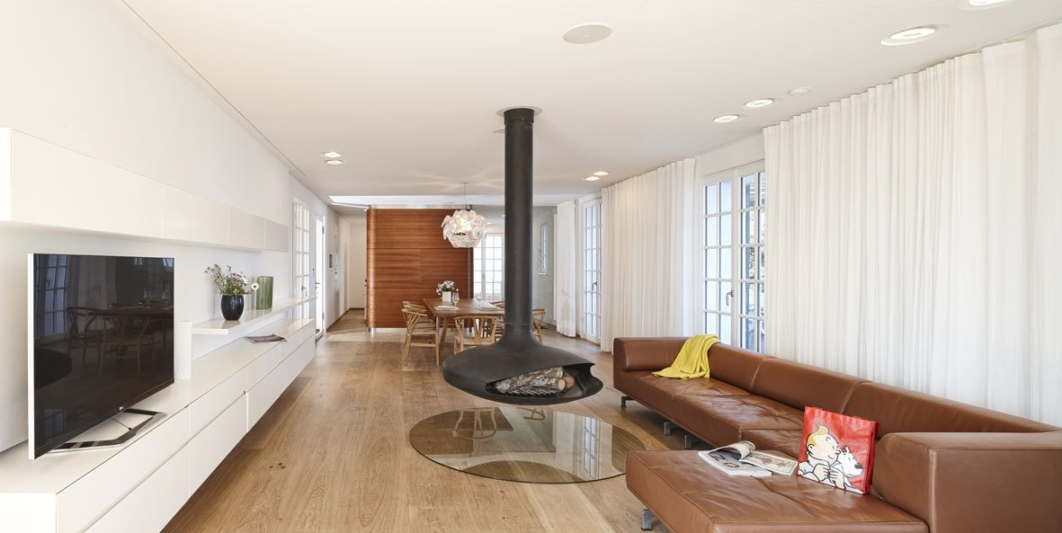 One of the biggest parts of the remodel was removing walls on the ground floor to make space for more of an open plan. The hanging steel Gyrofocus Fireplace by Focus gives the living room a unique character. It's flanked by a Delphi sofa from Erik Jørgensen. Tagged: Living Room, Hanging Fireplace, Medium Hardwood Floor, and Sofa.  Photo 4 of 9 in A Renovated Modernist Oasis in the French Riviera from Modern Mediterranean Homes