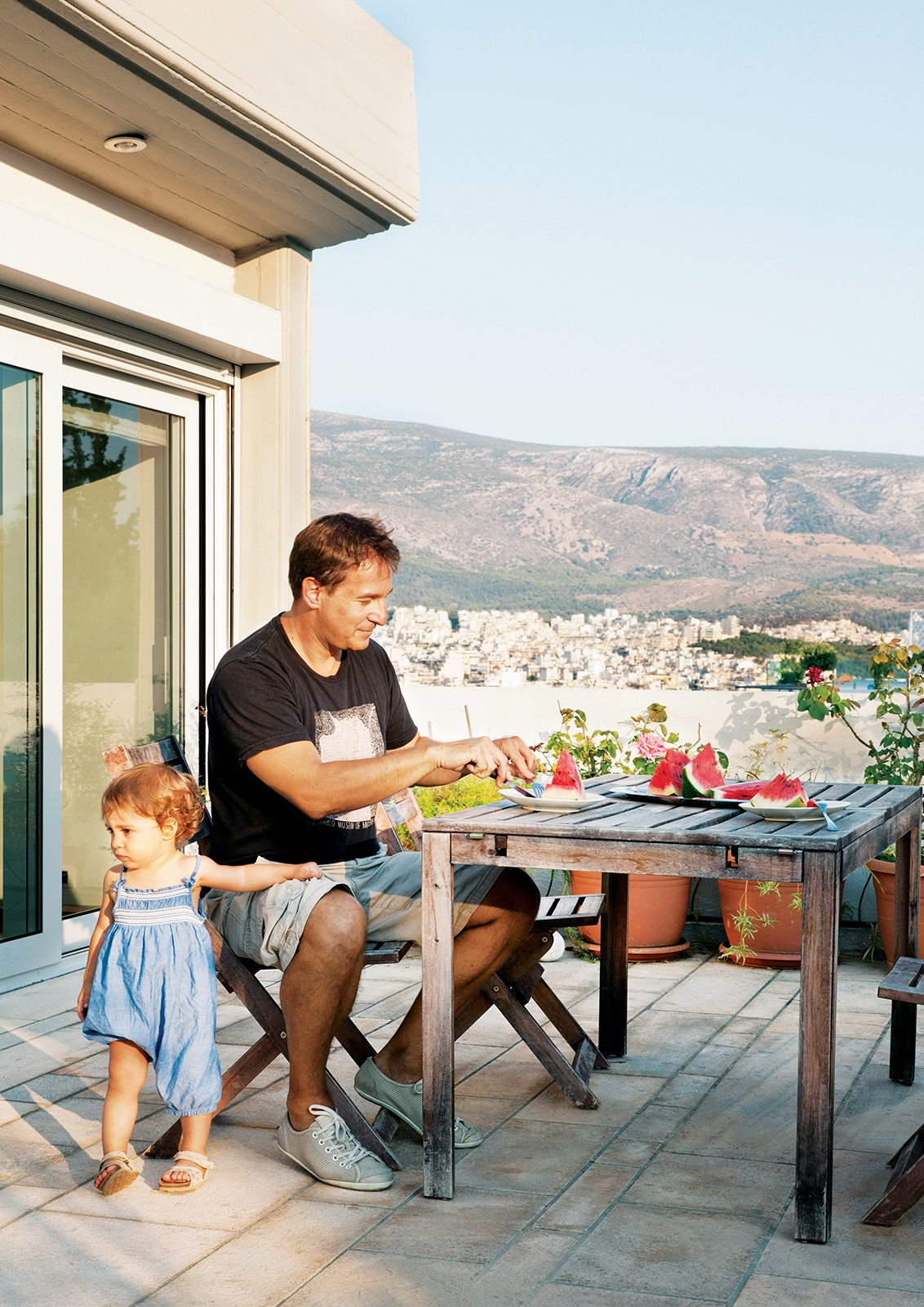 """Outdoor and Pavers Patio, Porch, Deck Vassiliou and Angeliki tuck into watermelon slices on a patio off the master bedroom. The terrace offers views of Mount Lycabettus, whose peak towers 745 feet above Athens, and the city itself, which splays out toward the mountains in the distance.  Search """"terrace"""" from Odd Angles Don't Stop This Apartment's Transformation"""