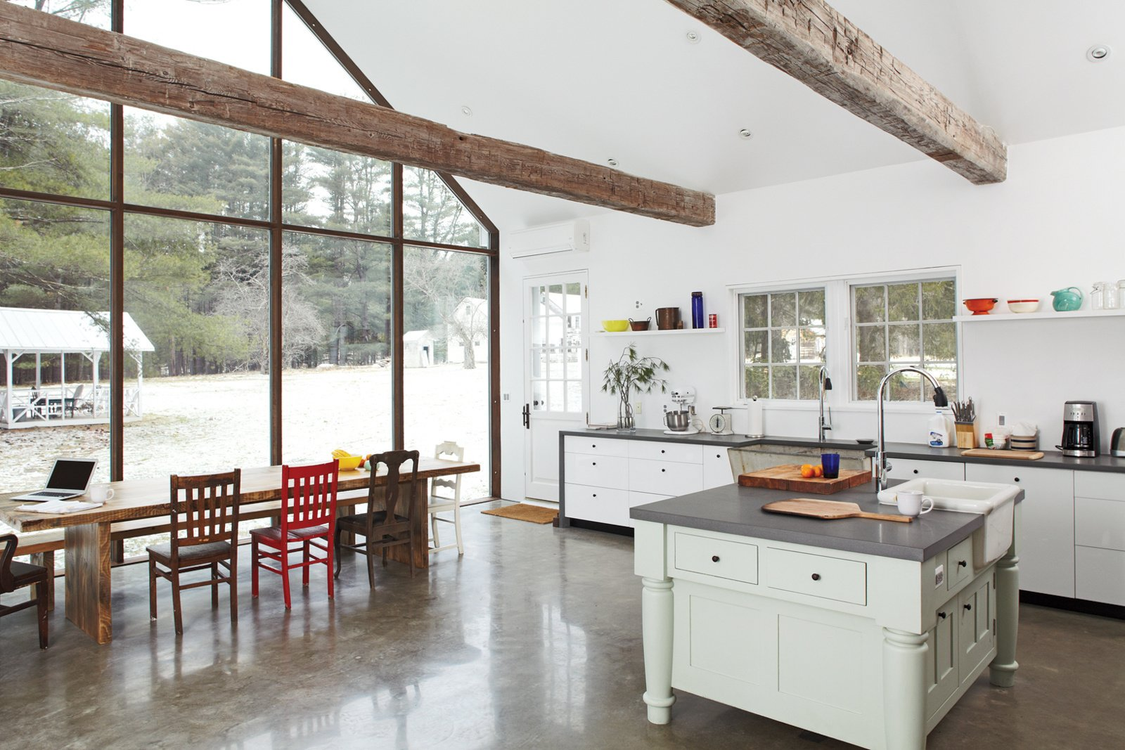 """Homeowner Tom Givone states, """"The hope has been to combine archaic and modern elements in a way that would enhance the beauty of each by virtue of its contrast with the other."""" While the table is situated in front of the house's rear wall of skyscraper glass. The laminated kitchen cabinets by Ikea are framed in wraparound bluestone; the 48-inch commercial range is by FiveStar. Photo by: Mark Mahaney  Kitchens We Love: Part 2 by Jami Smith from Ways to Modernize a Farmhouse"""
