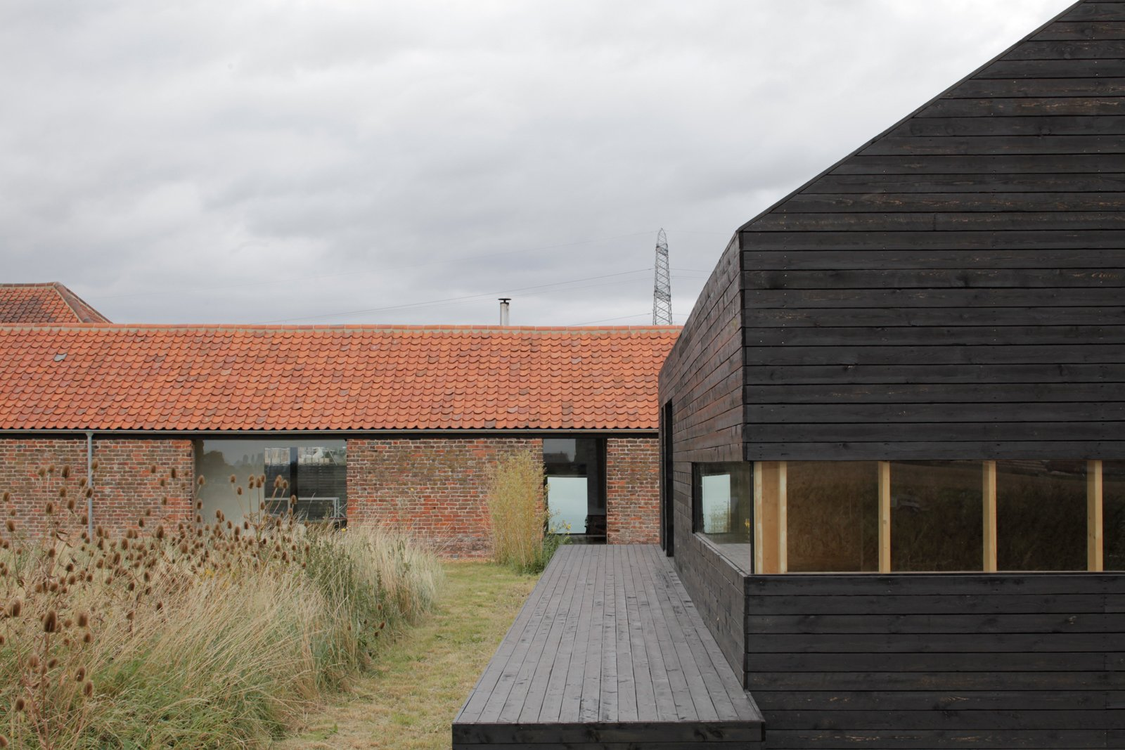 Exterior, Tile Roof Material, Brick Siding Material, Wood Siding Material, and House Building Type For a bit of elevation in the overwhelmingly horizontal compound, step onto the deck of the Stealth Barn. A strip of mowed grass delineates a path between the two structures; otherwise the grasses grow wild.  Photos from A Pair of English Barns Hide Unabashedly Bold and Budget-Friendly Minimalist Interiors