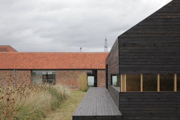 For a bit of elevation in the overwhelmingly horizontal compound, step onto the deck of the Stealth Barn. A strip of mowed grass delineates a path between the two structures; otherwise the grasses grow wild.