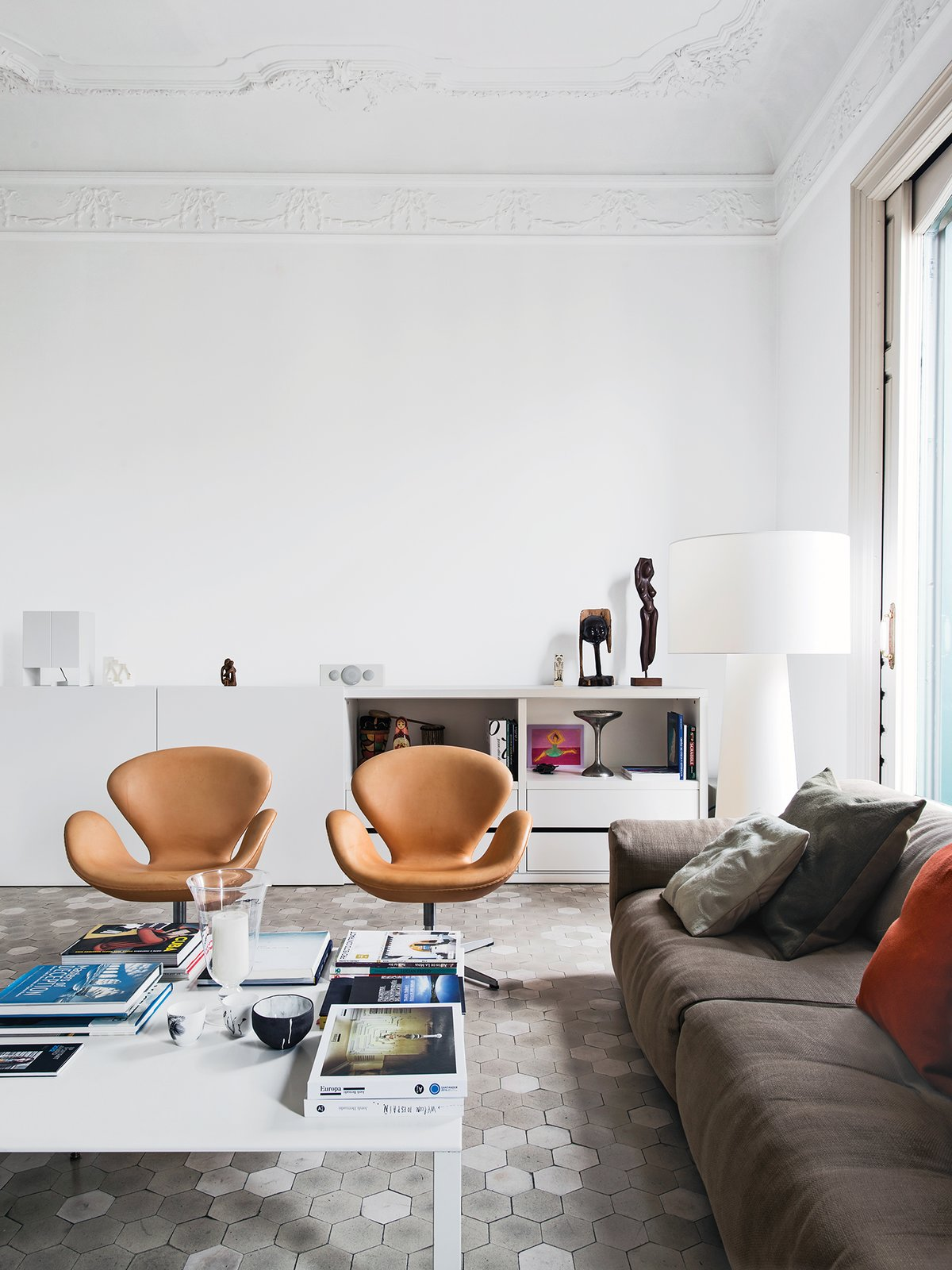 """Living Room, Chair, Sofa, and Coffee Tables In the living room of the Barcelona apartment designer Elina Vila D'Acosta-Calheiros shares with her husband, Ginés Gorriz, Arne Jacobsen Swan chairs join a sofa by Piero Lissoni for Living Divani. The cabinet is from Cappellini, as is the Marcel Wanders Big Shadow lamp.  Search """"chieftains chair"""" from Meet Marcel Wanders, 2015 Dwell on Design Keynote Speaker"""