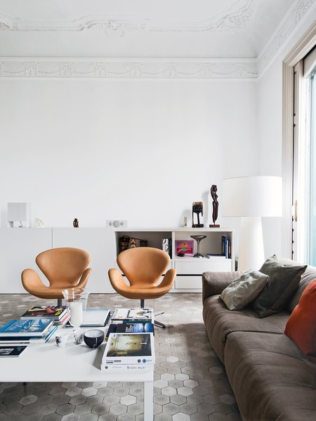 In the living room of the Barcelona apartment designer Elina Vila D'Acosta-Calheiros shares with her husband, Ginés Gorriz, Arne Jacobsen Swan chairs join a sofa by Piero Lissoni for Living Divani. The cabinet is from Cappellini, as is the Marcel Wanders Big Shadow lamp.