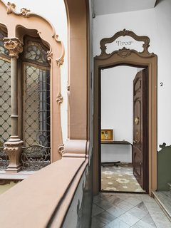 The ornate facade of the Art Nouveau building carries over into the entrance. The floral pattern of the original tile floor begins in the entrance hall and continues throughout the apartment; it is offset by a sleek iron table from Minim.