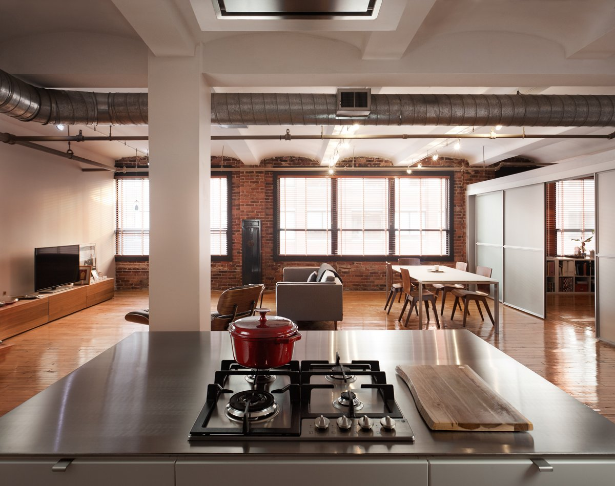 "Kitchen and Cooktops The building was built in 1910. ""It's a pretty raw space with rough exposed brick, barrel vaulted ceilings, original hardwoods, and exposed ducting,"" Greenawalt says. ""We tried to use industrial materials—stainless steel, perforated steel, brick—in a more refined way for the kitchen.""  Loft from Clever Red Pegboard Backsplash in a Remodeled Kitchen"