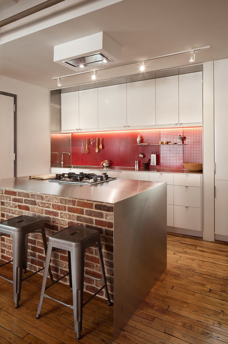 Kitchen, White, Metal, Range Hood, Range, Mosaic Tile, Drop In, Track, and Medium Hardwood A Boston loft in a former textile factory receives a minimal, efficient kitchen at the hands of Bunker Workshop. In the kitchen, the island features a stainless steel countertop with a gas cooktop, oven, and a brick half wall.  Best Kitchen Metal Range Photos from Clever Red Pegboard Backsplash in a Remodeled Kitchen