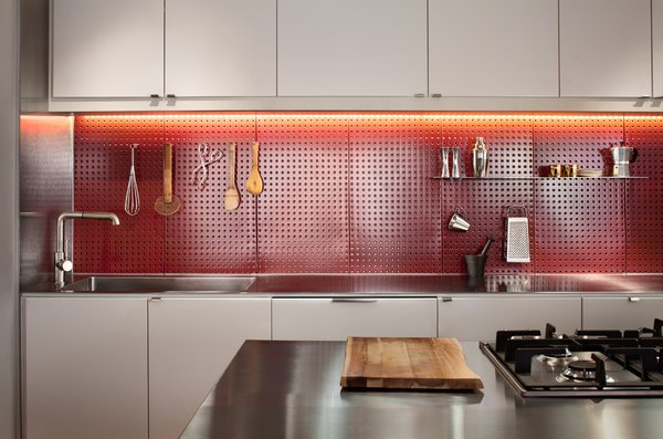 The client wanted to be able to prepare meals efficiently. A red steel pegboard backsplash lets him easily access cooking utensils. The cabinets are Ikea.