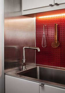A Boston loft in a former textile factory receives a minimal, efficient kitchen at the hands of Bunker Workshop. The client wanted to be able to prepare meals efficiently, so a red steel pegboard backsplash lets him easily access cooking utensils. The cabinets are IKEA.