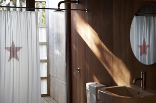 The cedar plywood paneling used throughout the project adds a mellow quality to the light. The dropped fiberglass screen recalls an outdoor shower, but also provides privacy.  The materials were chosen for their texture, weathering characteristics, durability, and organic appearance — while fiberglass may not actually be natural, says architect Lance Herbst, the type used here, with its visible fibers, has a natural quality.  The basin is Metrix, and the shower curtain by Catherine David.