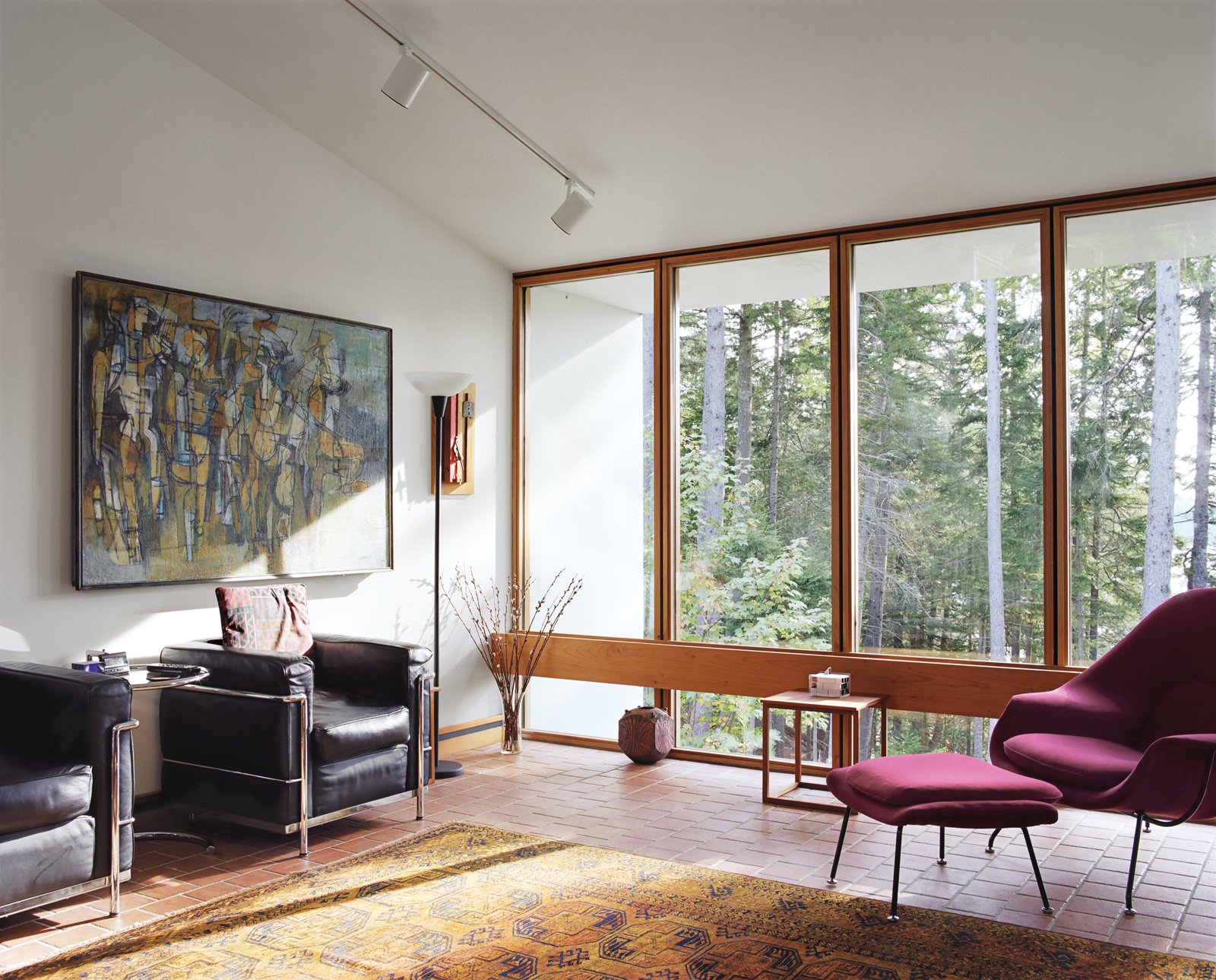 A pair of LC2 chairs by Le Corbusier are ideal spots for watching the river down below. The Womb chair by Eero Saarinen is a close second.  Photo 7 of 15 in The Right Track