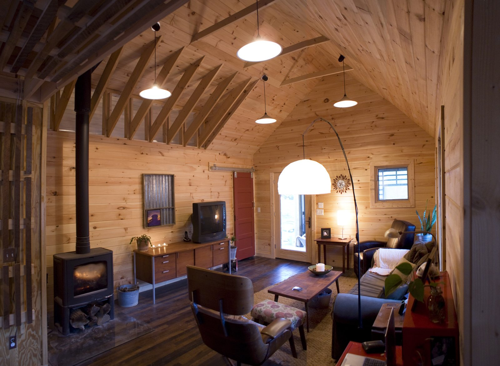Inside the main living area, tongue-and-grooved white pine covers the walls and vaulted ceilings, and a red closet door, built of salvaged pine from the original house, slides open and closed on barn track hardware.  Photo 4 of 13 in Farmhouse Redux