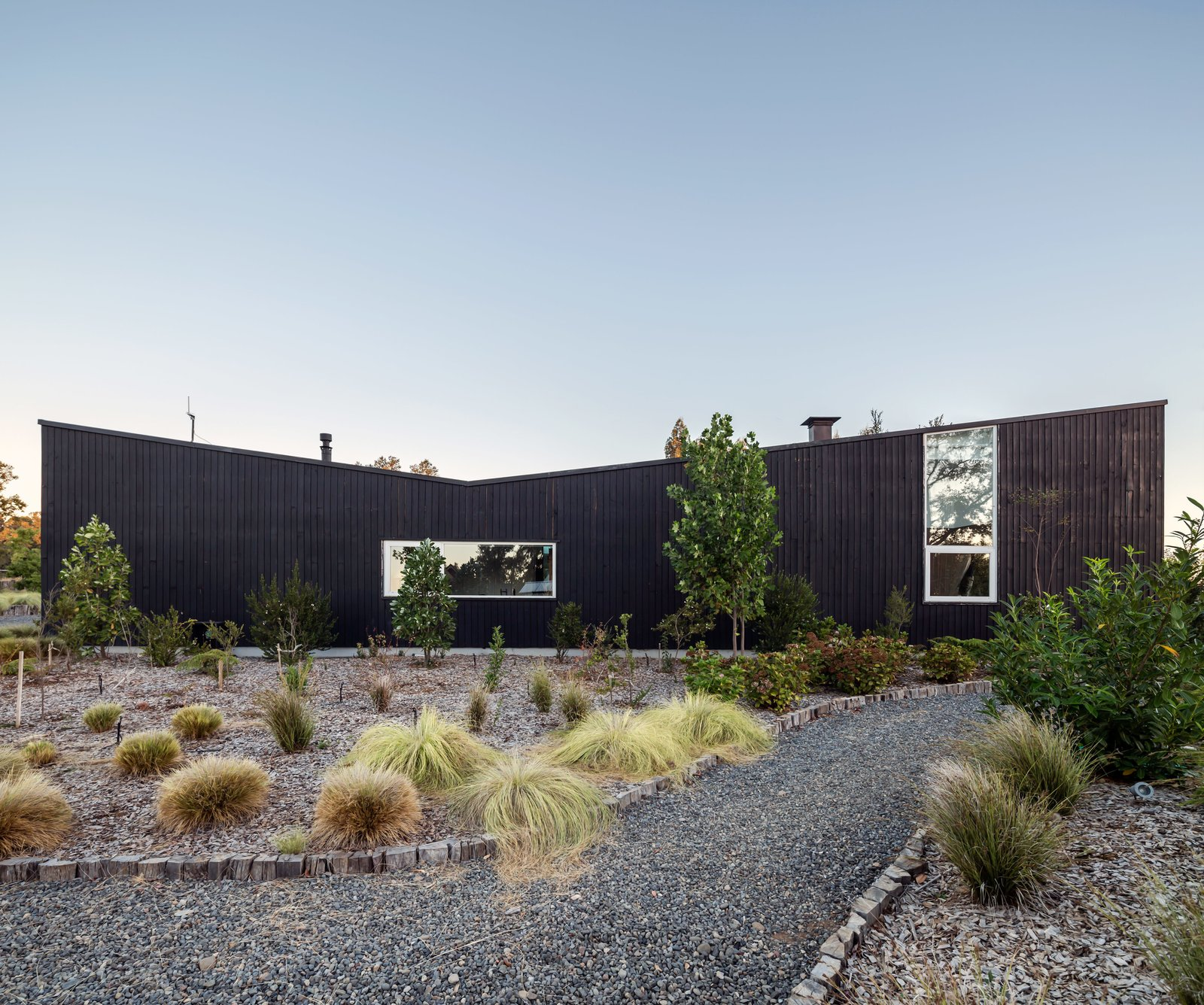 Outdoor, Front Yard, Walkways, Trees, and Grass A Chilean home's dramatic stained-pine exterior references local vernacular architecture.  Photos from This Chilean House Recreates the Hot Spring Experience With a Super Luxurious Stone Tub