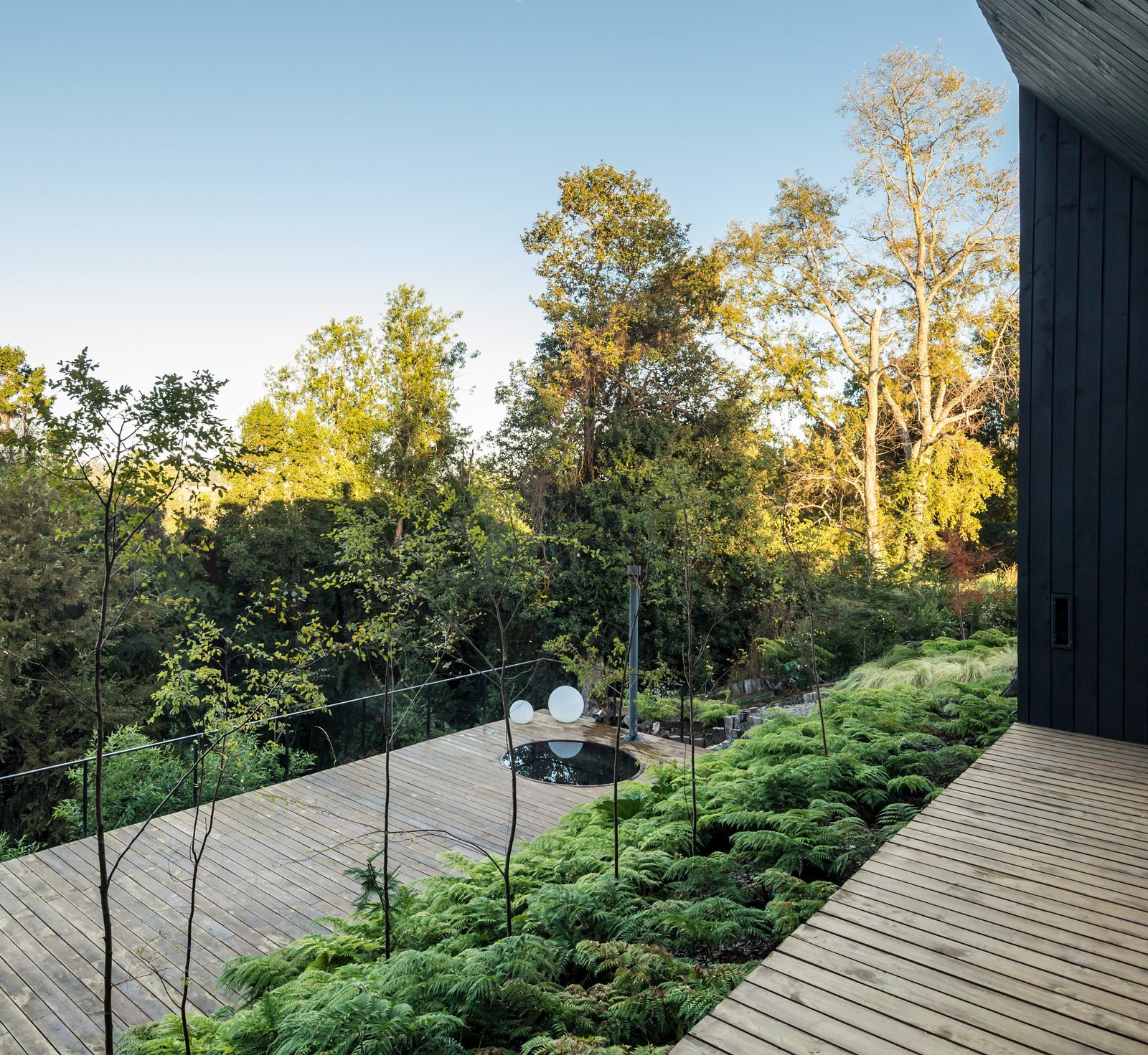 """Outdoor, Trees, and Wood Patio, Porch, Deck The lower terrace, which features a hot tub, is farther down the hill to immerse its users in the landscape.  Search """"terrace"""" from This Chilean House Recreates the Hot Spring Experience With a Super Luxurious Stone Tub"""