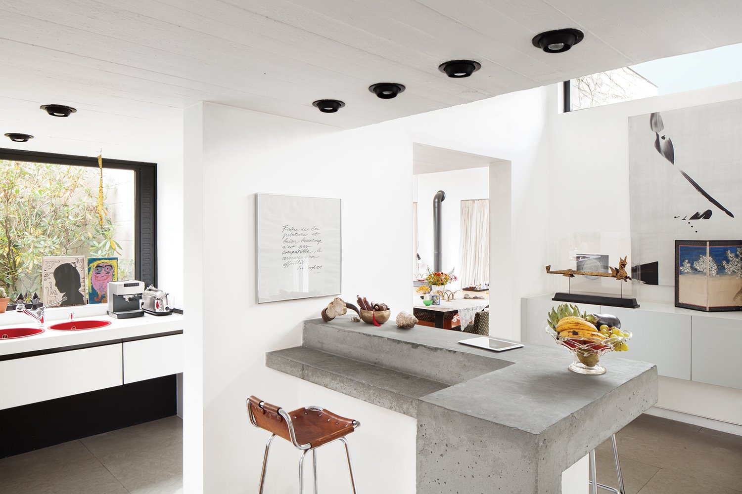 Kitchen, Concrete, Recessed, White, and Cement Tile Smitten from the start with a 1970s concrete villa in rural Belgium, a resident and her designer embark on a sensitive renovation that excises the bad (carpeted walls, dark rooms) and highlights the good (idyllic setting, statement architecture). Owner Nathalie Vandemoortele worked with designer Renaud de Poorter on the interior renovations, which included opening up the heavy structure with the help of new windows and doors to the outside. A concrete bi-level island keeps the Brutalist vibe on the interior, but is open and light enough to feel balanced.  Best Kitchen White Cement Tile Photos from A Concrete Home in Rural Belgium
