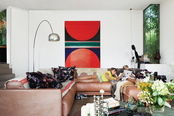 De Poorter lowered the living room floor by about three feet to allow for larger windows. Vintage Sade sofas, purchased in Berlin, join an Arco lamp by Achille Castiglioni for Flos, a Noguchi coffee table, and a painting by family friend Hugo de Clercq.