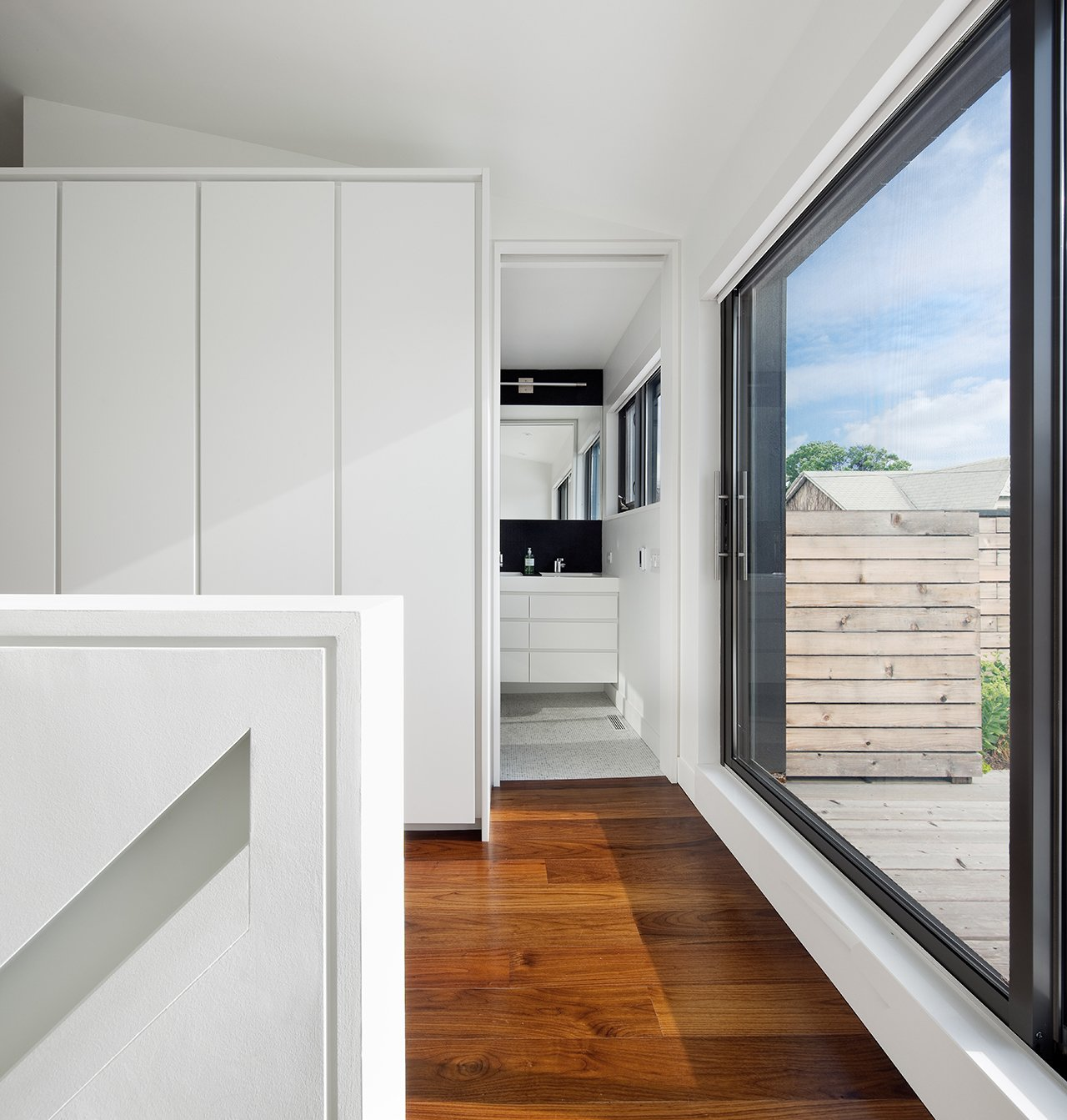 """Directly at the top of the stairs on the third story, oversized sliding glass doors lead out to a sunny roof deck. To the left, an ensuite bathroom is furnished with Duravit and Wetstyle fixtures. """"It has tiny white tumbled marble mosaic tiles, which are very soft underfoot,"""" Dubbeldam says.  Contrast House by Laura C. Mallonee"""