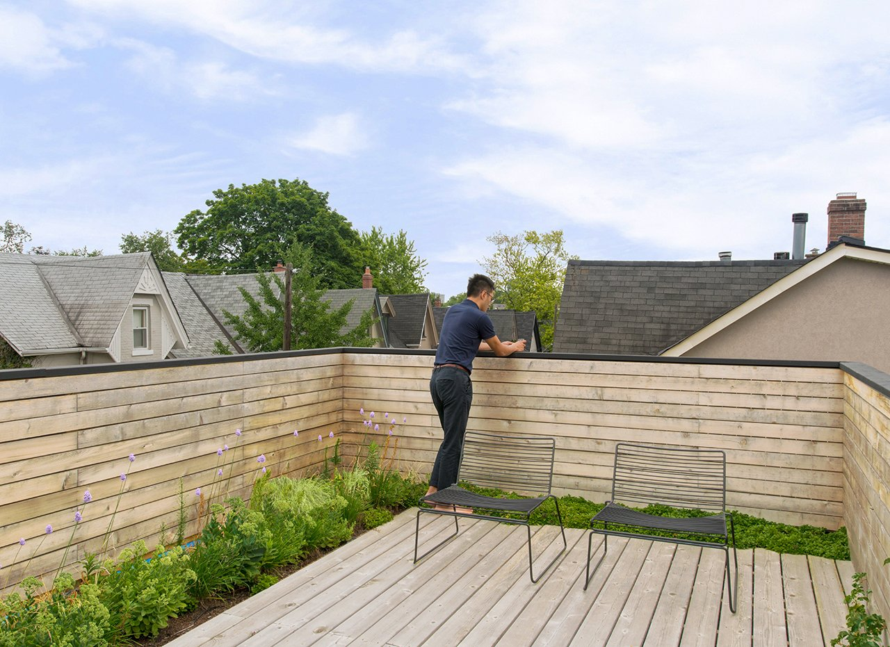 "Outdoor, Rooftop, Wood Patio, Porch, Deck, Decking Patio, Porch, Deck, Flowers, Gardens, Horizontal Fences, Wall, and Wood Fences, Wall Two Harry Bertoia-designed chairs sit on the main third story deck, which includes a hidden green roof that absorbs rainwater, cools the upper floors, and purifies the air. ""It's a nice little oasis on the roof, with plants that bloom at different times of year. The owners love spending time up there,"" Dubbeldam says.  Contrast House by Laura C. Mallonee"