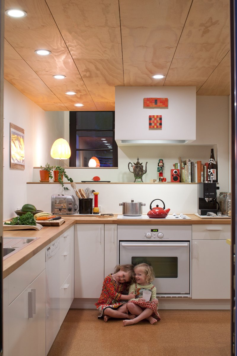 Kitchen, White, Wood, Drop In, Recessed, Cooktops, Cork, and Wall Oven Pippa (left) and Maisie (right) play in the kitchen. Though Hale and Edmonds would have preferred Bosch appliances, a deal at Ikea was too good to pass up. They purchased all of the cabinets and appliances (a combination that earned them 20-percent off the total) for a mere $4,700.  Best Kitchen Recessed Drop In Wall Oven Cork Photos from A New Slant