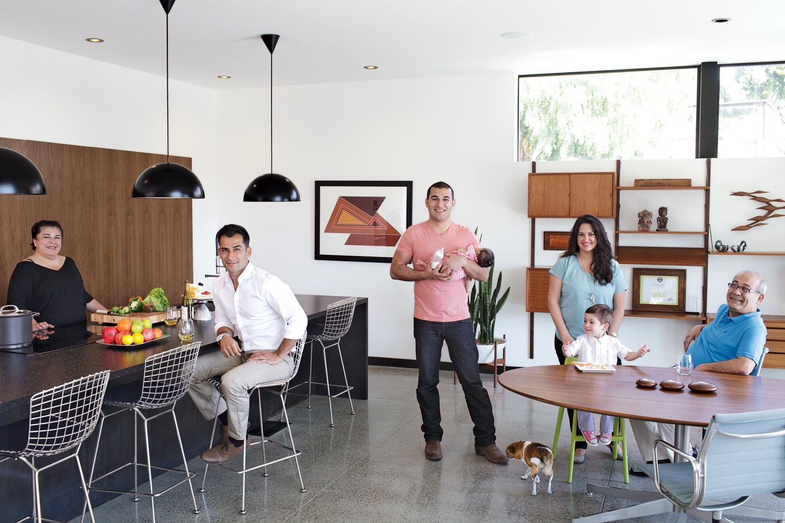Dining, Concrete, Table, Recessed, Chair, Bar, Pendant, Stools, and Shelves Parents Mitra and Sasan Nakhshab join sons Nima and Soheil (with daughter, Sofia) and Soheil's girlfriend, Susana Mora (with son, Shayan), on the main floor.  Best Dining Shelves Table Bar Pendant Photos from The First LEED Gold-Certified Family Home in San Diego