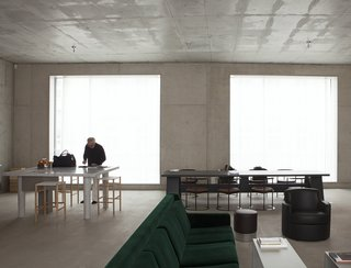 "DAVID CHIPPERFIELD   ""First his studio, then his home. David Chipperfield chose Berlin, after the city commissioned him to rebuild the Neues Museum in 1997. It is in the same neighborhood, Mitte. In the courtyard that contains both his house and his studio, Chipperfield also designed a canteen, a place where locals meet. The house is built of concrete, with large windows overlooking the street and the courtyard. It contains a few '50s and '60s Italian furnishings, and two colours. The green of a velvet sofa and the orange of a bookcase that divides the space between the kitchen and the sitting room."" Photo by Davide Pizzigoni."