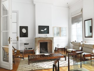 "The drawing room, the couple's principal entertaining space, contains many highlights of the exhibition, including two Tonico lounge chairs by Sergio Rodrigues; a jacaranda bench by Alberto Reis; a leather-and-rosewood sling chair fabricated by Liceu de Artes e Oficios de São Paulo; and drawings by the contemporary Brazilian artist Paulo Climachauska. ""Furniture is more beautiful with a patina—and this comes from years of careful and loving use."" —Kathryn Smith"