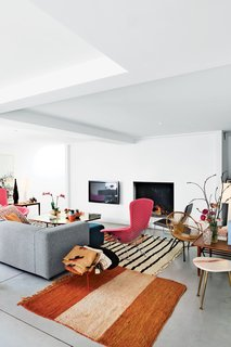 In the home of two interior architects the marble-topped occasional table and the wood table are vintage, the antique rugs are from Morocco, a Low Pad chair by Jasper Morrison for Cappellini sits near the fireplace, and the brass-and-steel coffee table was designed by Poorter and Holdrinet. But the stars of the living room are still a pair of pink Bird chairs Bertoia for Knoll. Photo by Frederik Vercruysse.