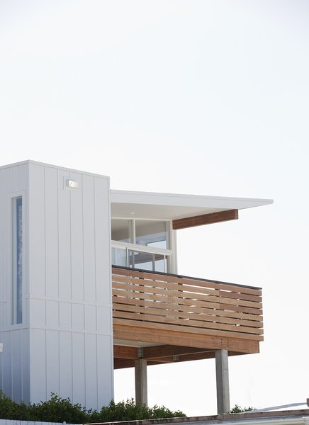 All-vinyl siding on the original shell was replaced with natural plywood T1-11 cladding. The second story features engineered brushbox wood plank, as well as Batu decking for the railing and lanai (a sheltered, open-sided patio).