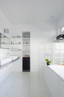 The bathroom's glass block partition is just one example of the extensive list of repurposed materials used for this project. The sinks are from IKEA and bathtub is from Home Depot.