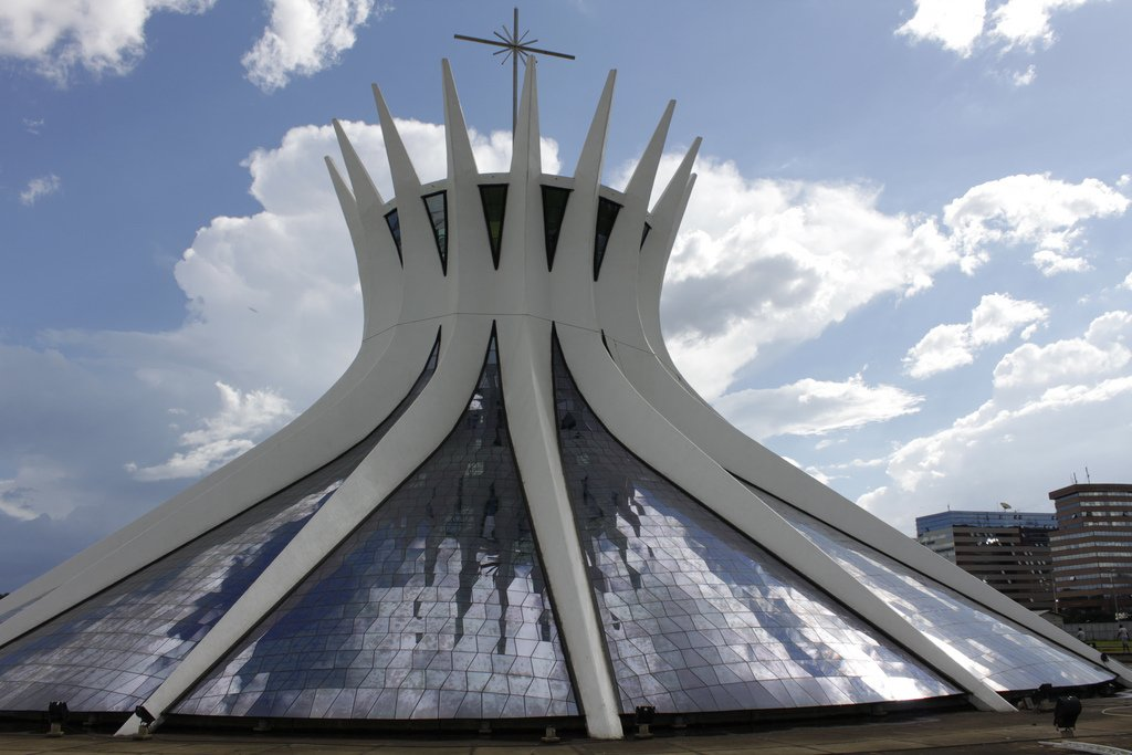 Cathedral of Brasilia  Brasilia, Brazil (1970)  The tent-like shape of this striking cathedral is formed by 16 curved pillars, jutting towards the sky like the fingers of a hand in prayer. Sunlight enters the roof through a wavy mosaic of blue, white and brown tiles. Photo by Edward Stojakovic.  Photo 4 of 10 in Design Icon: Oscar Niemeyer