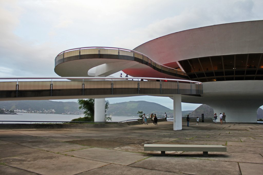"Outdoor and Concrete Patio, Porch, Deck ""A flower that rises from the rock"" is how Niemeyer described this organic, saucer-like structure, a home for art and design that boasts beautiful views of Guanabara Bay. An inviting red walkway snakes up towards the entrance towards the main cupola.  Photo 6 of 11 in Design Icon: Oscar Niemeyer"