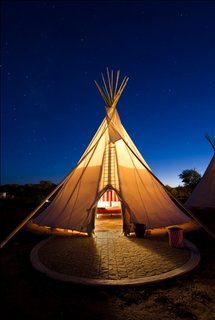 Here, one of El Cosmico's three teepees is a lantern for desert travelers.