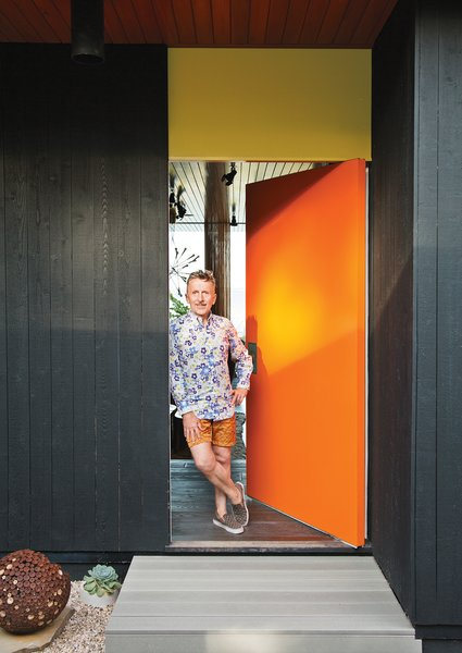 """Homeowner Simon Doonan stands next to the front door. """"We have flamboyance, and we're not inhibited about anything. [Architect] Gray Organschi gave [the house] that intellectual rigor needed to make it beautiful. We were well matched."""""""