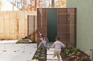 An outdoor shower in the lower courtyard includes most of the materials that define the project, including Cor-Ten steel posts, horizontal ipe slats and decking, a custom seat and towel shelf set into a natural boulder, and concrete pavers. The yard includes many elements built for play, like a water feature embedded in a concrete wall that is fed by runoff rainwater collected from the breezeway roof.