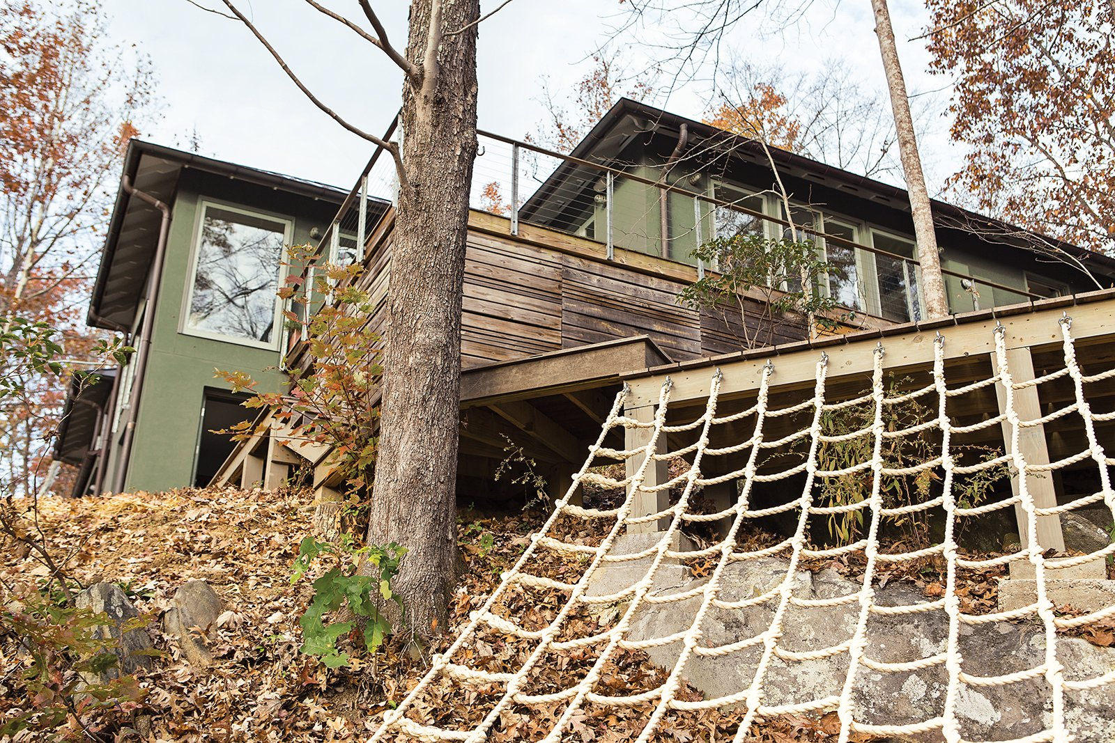 Exterior, House Building Type, Stucco Siding Material, and Wood Siding Material Another backyard hotspot is the deck, built around an existing boulder, where adults can lounge while the kids climb.  Photo 8 of 16 in How This Landscape Design Made a Home as Fun as a Playground