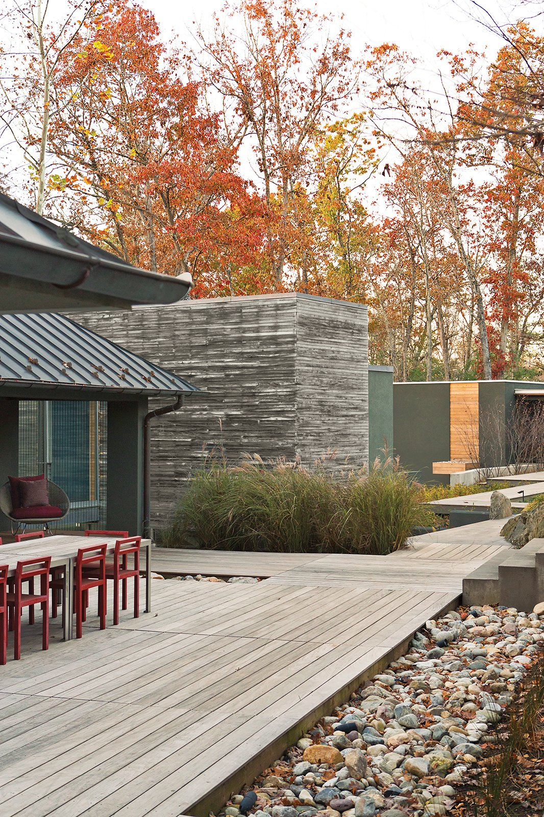 Outdoor, Walkways, Wood Patio, Porch, Deck, and Large Patio, Porch, Deck The dining table, a custom design by Formwork, and red Non chairs by Komplot complement the addition's cypress cladding.  Photo 10 of 16 in How This Landscape Design Made a Home as Fun as a Playground