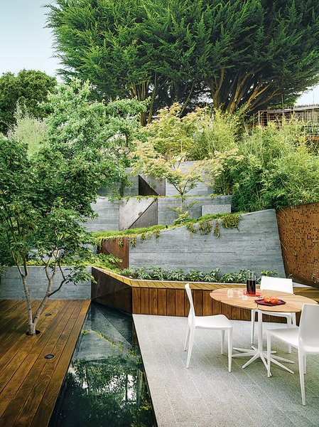 A maple tree grows through an ipe deck in this garden that Mary Barensfeld designed for a family in Berkeley, California. A reflecting pool separates it from a granite patio, which is furnished with a Petal dining table by Richard Schultz and chairs by Mario Bellini. The 1,150-square-foot garden serves as an elegant transition from the couple's 1964 Japanese-style town house to a small, elevated terrace with views of San Francisco Bay. Filigreed Cor-Ten steel fence screens—perforated with a water-jet cutter to cast dappled shadows on a bench and the ground below—and zigzagging board-formed concrete retaining walls are examples.