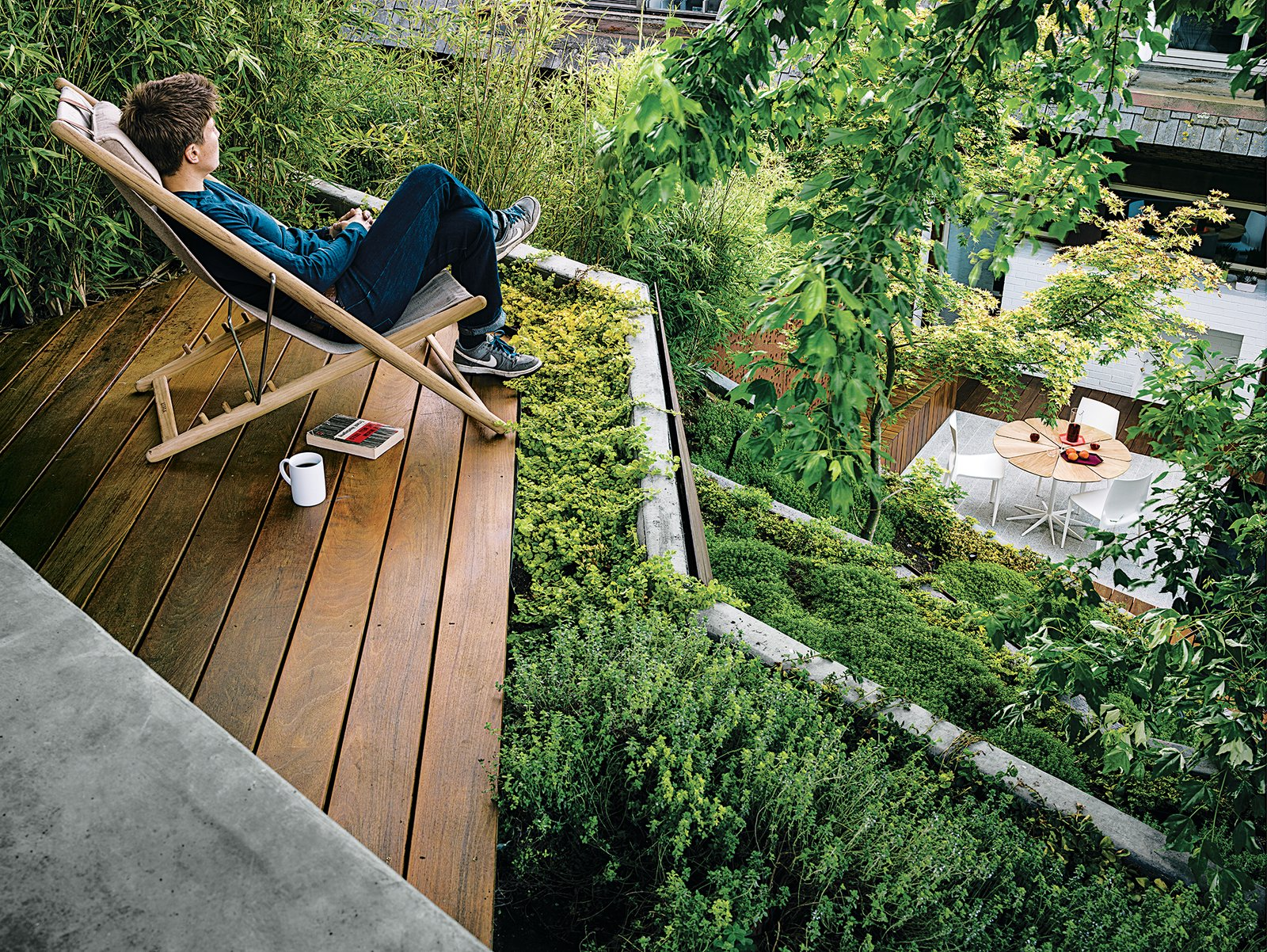 Outdoor, Small Patio, Porch, Deck, Shrubs, Trees, Wood Patio, Porch, Deck, and Back Yard A small terrace outfitted with an H55 easy chair by Björn Hultén offers a view of the San Francisco Bay.  Green Homes from Dwell's April Outdoors Issue by Kelsey Keith from An Architect's Tips for Creating a Garden in the Heart of the City